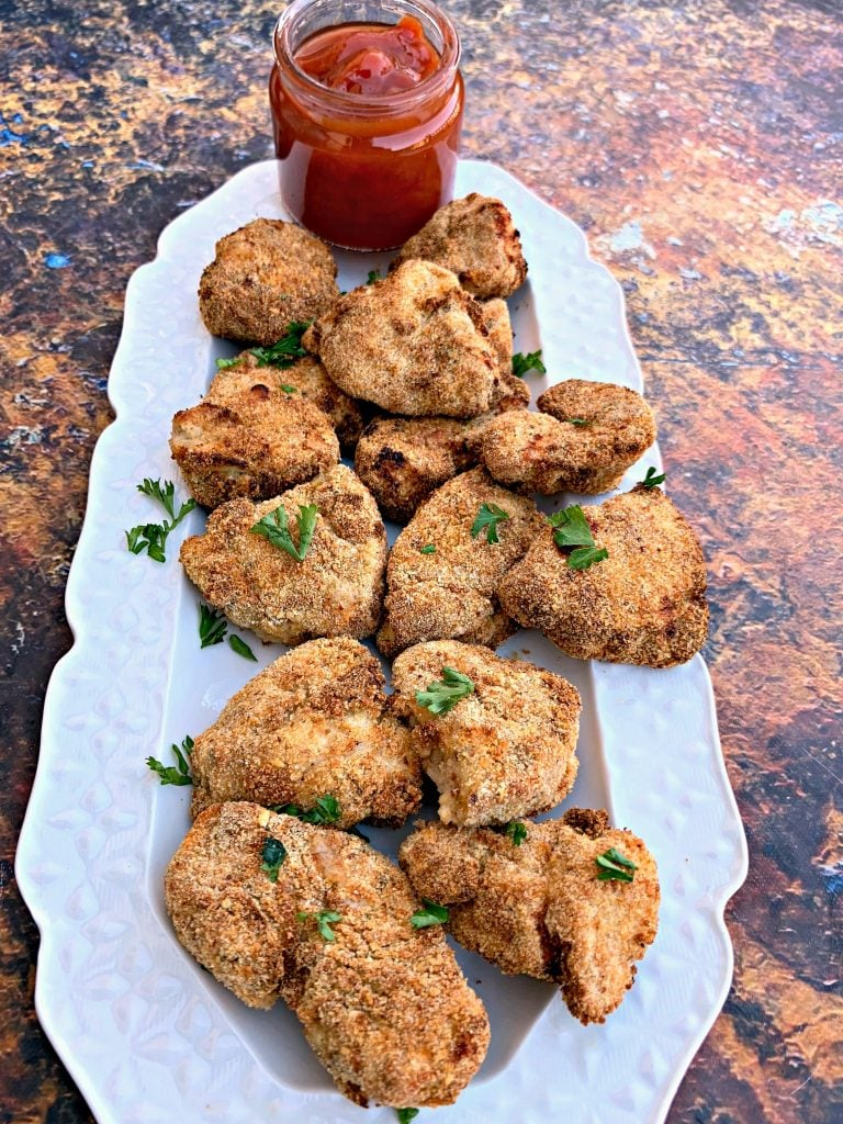 air fryer chicken nuggets on a white plate with ketchup
