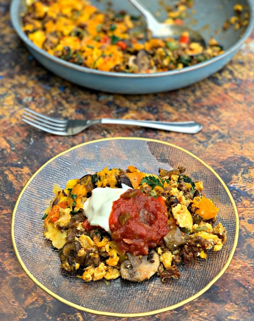 keto low carb sausage breakfast scramble on a plate with salsa and sour cream
