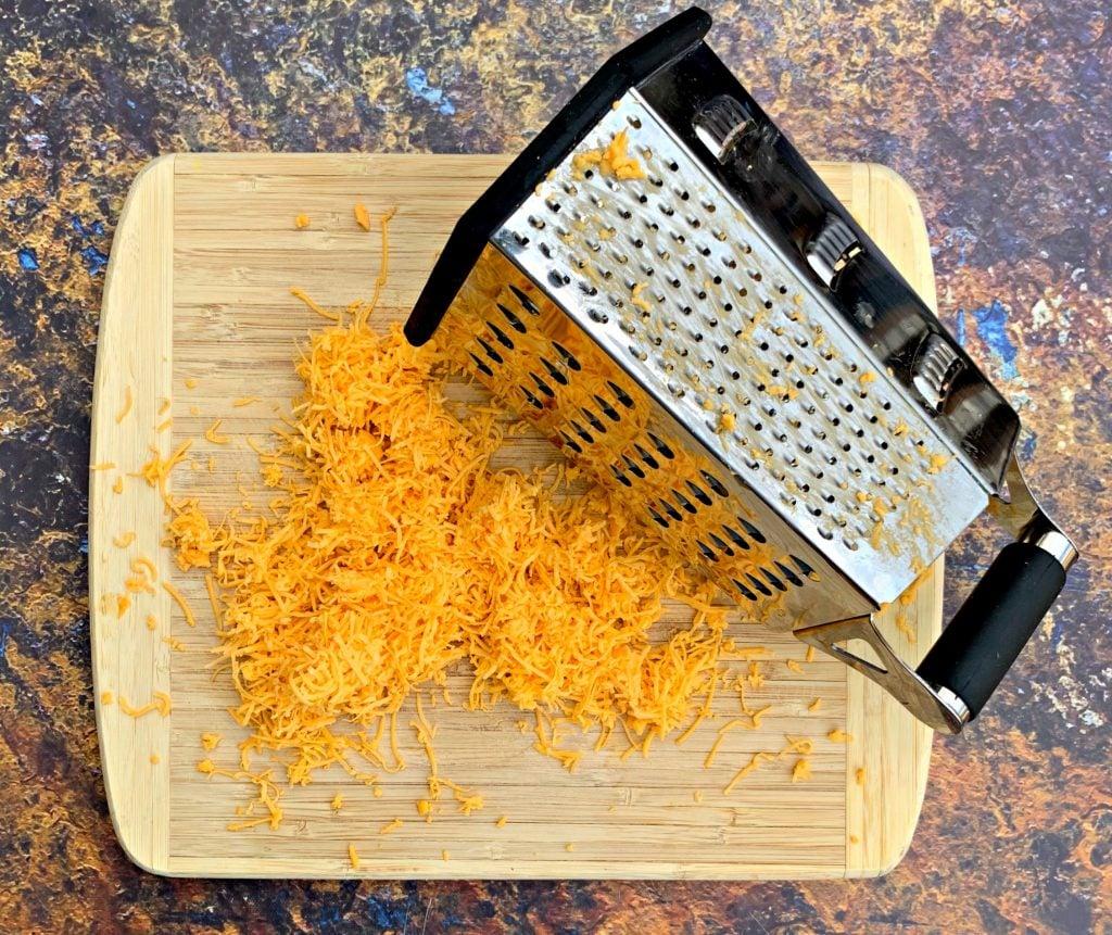 shredded cheddar on a cutting board with a grater