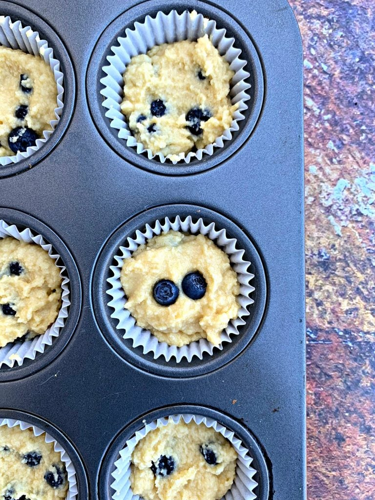 uncooked keto blueberry muffins in a muffin tin