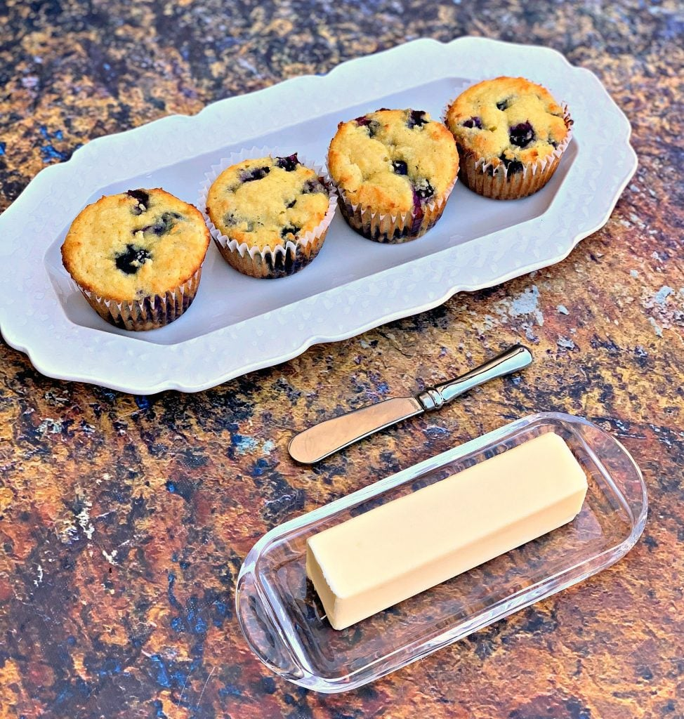 keto blueberry muffins on a white plate with a butter dish and a muffin tin with muffins