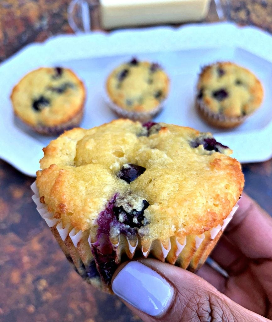 person holding keto blueberry muffins