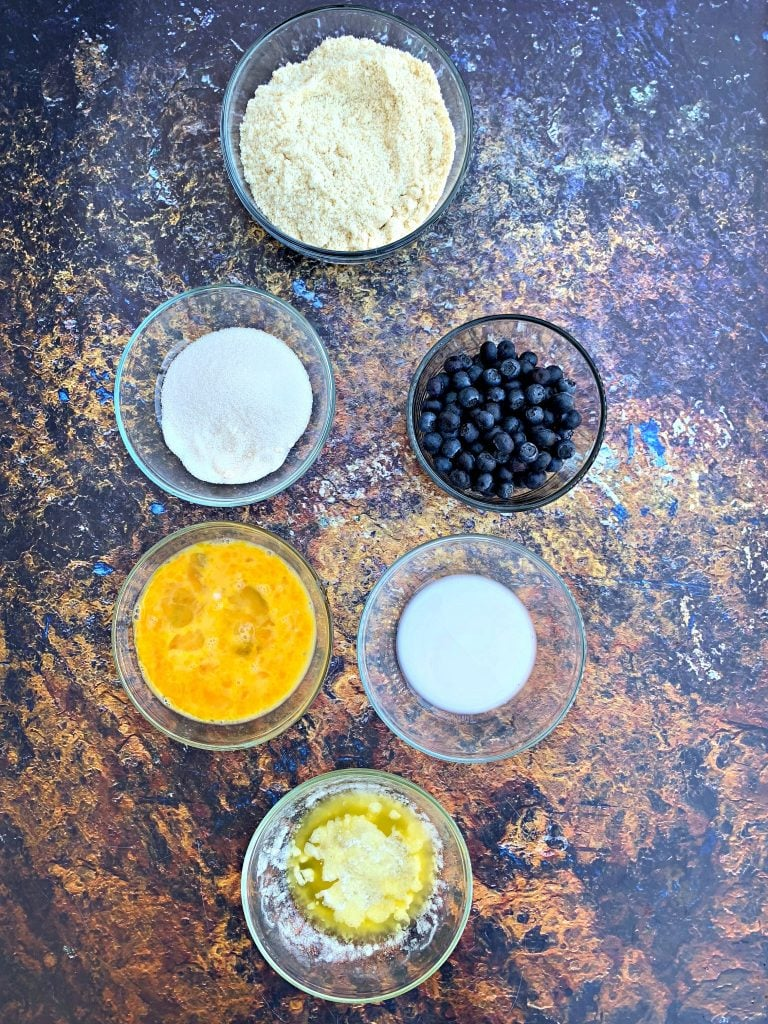 ingredients for keto blueberry muffins on a flat surface