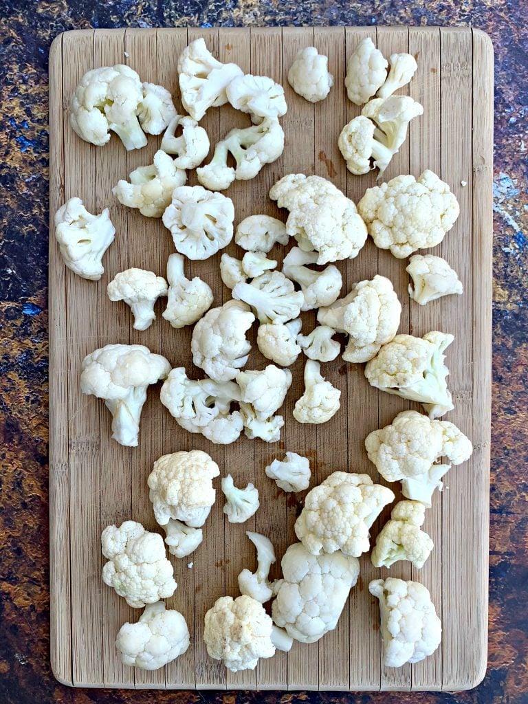 raw sliced cauliflower on a cutting board