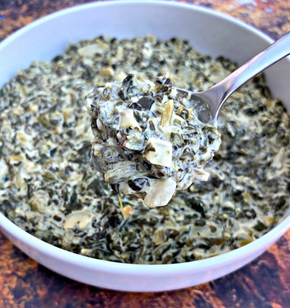a spoonful of keto low carb creamed spinach in a white bowl