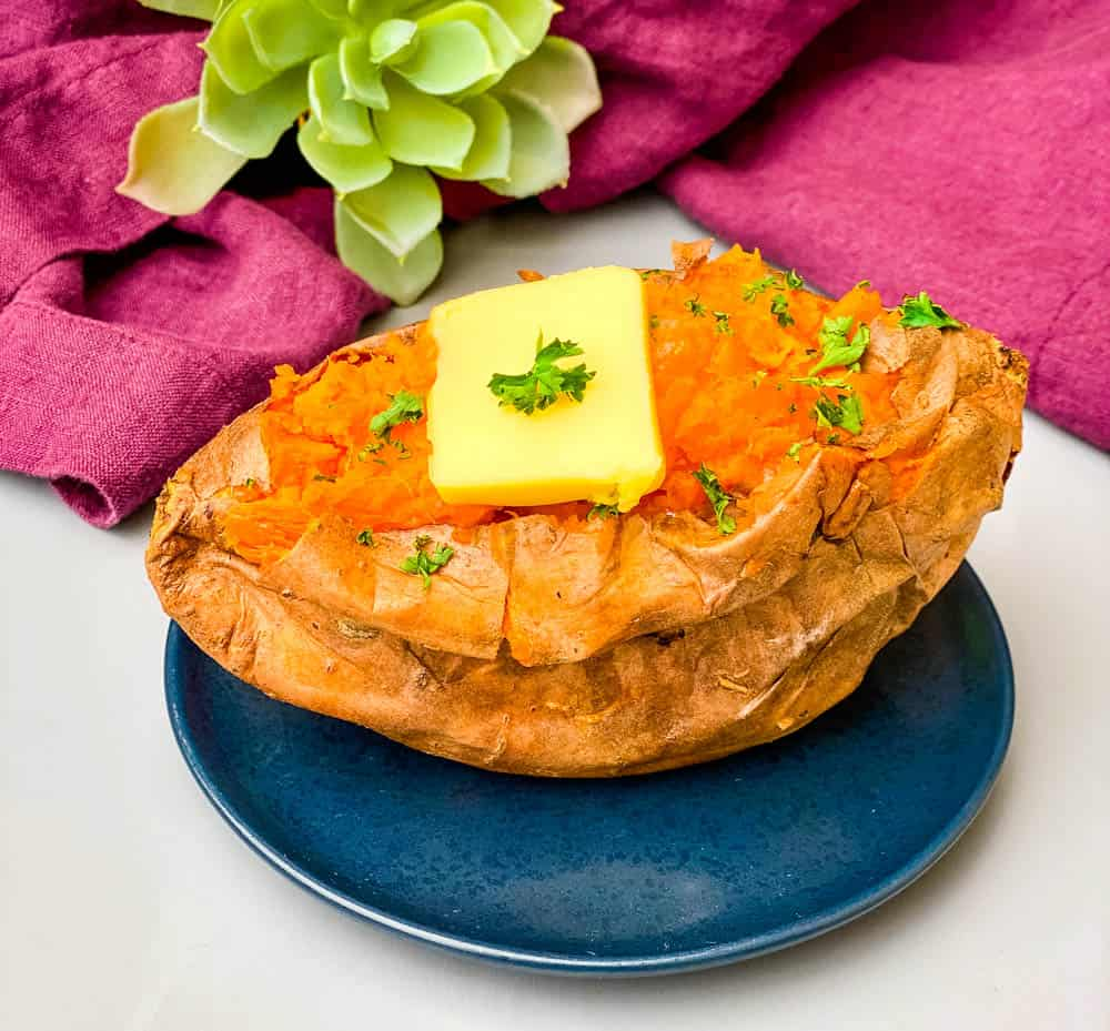 air fryer sweet potato on a blue plate with butter