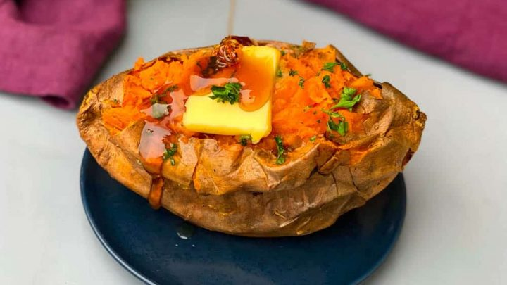 air fryer sweet potato with butter drizzled with honey on a blue plate