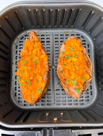 air fryer loaded sweet potatoes with butter and cinnamon on a white plate