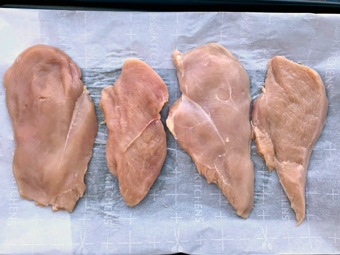 raw chicken breasts on parchment paper