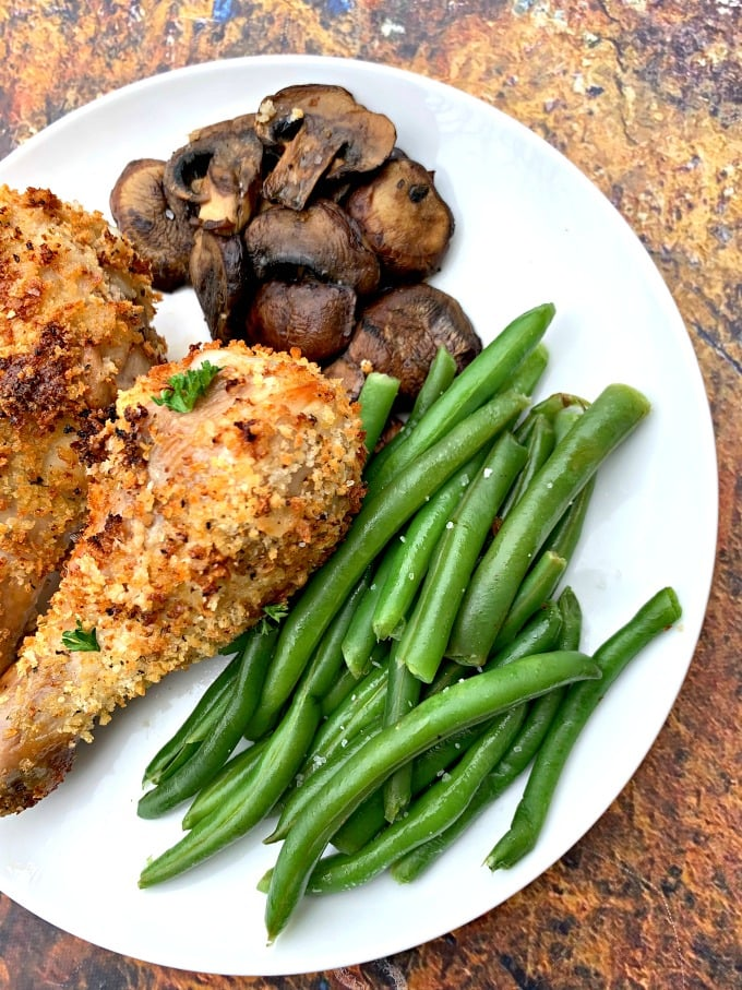 air fryer chicken drumsticks with green beans and mushrooms on a white plate