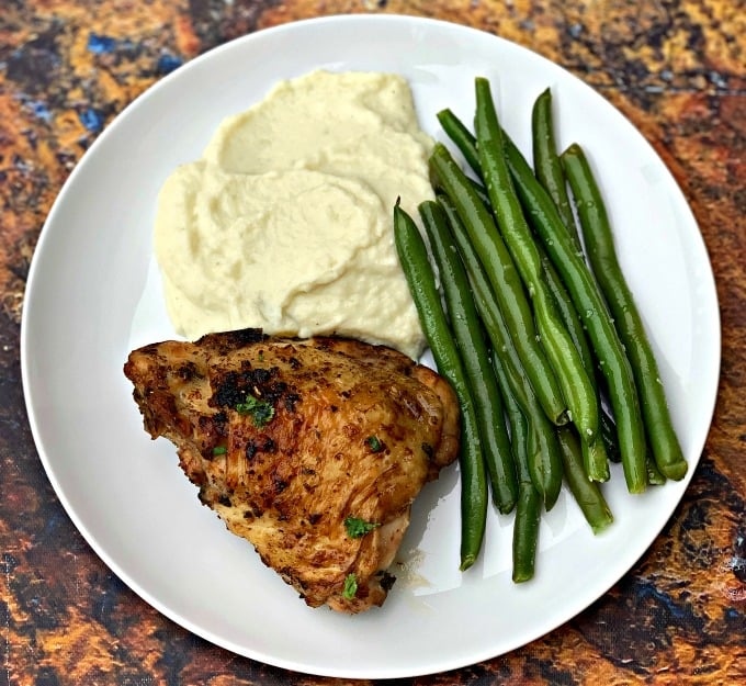 keto low carb air fryer cilantro lime chicken thighs in a white plate with cauliflower mash and green beans