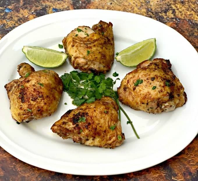 air fryer keto low carb cilantro lime chicken thighs on a white plate with lime and fresh cilantro