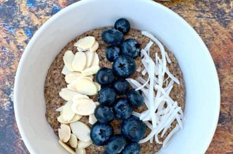 keto hemp oatmeal with blueberries, almonds, and coconut in a white bowl