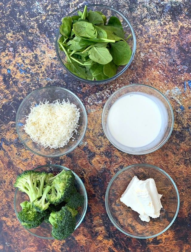 ingredients for keto chicken alfredo with broccoli and spinach in a skillet