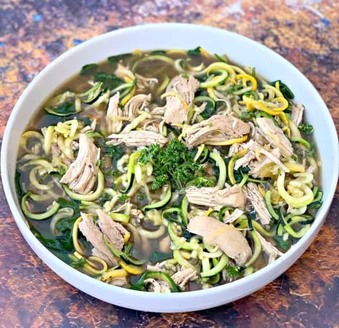 keto low carb chicken noodle soup with zucchini noodles in a white bowl