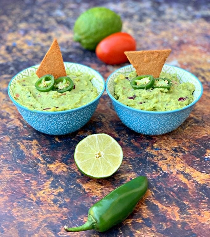 keto guacamole with low carb keto chips in blue bowls with fresh vegetables