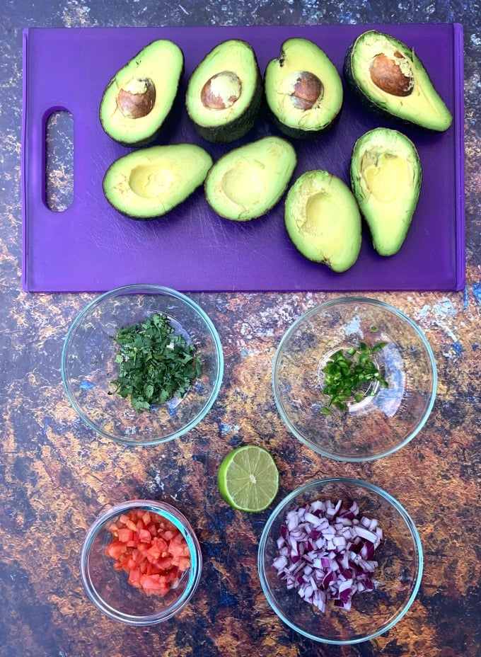 ingredients for keto guacamole avocado, cilantro, tomatoes, and lime in bowls