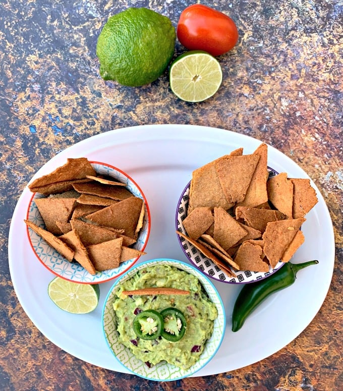 keto tortilla chips in bowls on a plate with guacamole and vegetables
