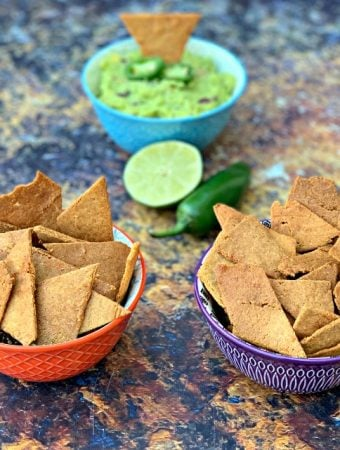 keto tortilla chips in bowls with guacamole and vegetables