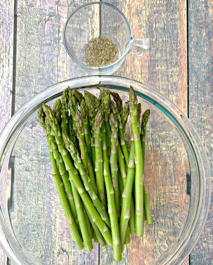 raw asparagus in a glass bowl