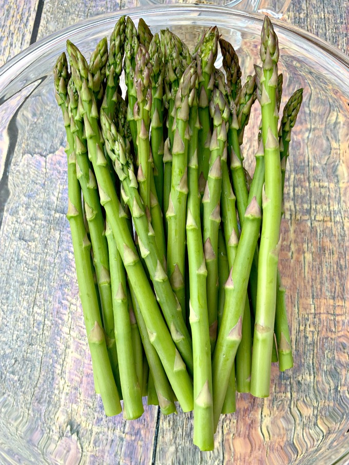 raw asparagus in a glass bowl