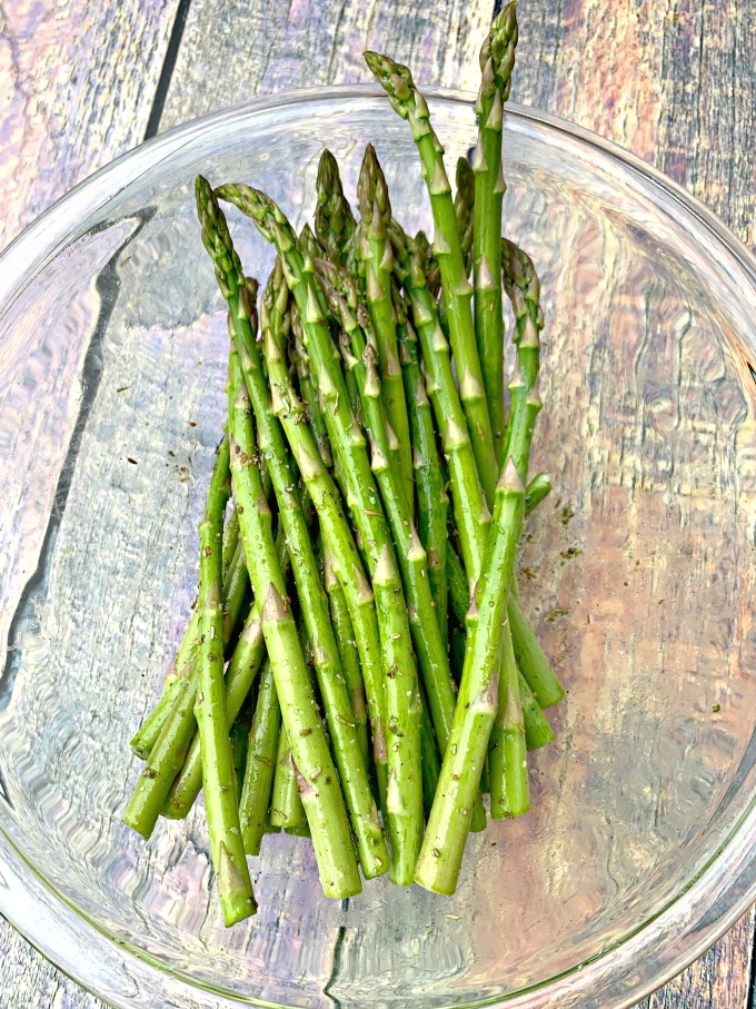 raw asparagus with olive oil in a glass bowl