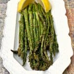 air fryer roasted asparagus on a white plate with lemon