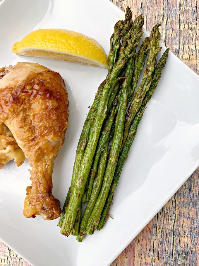 air fryer roasted asparagus on a white plate with lemon with chicken