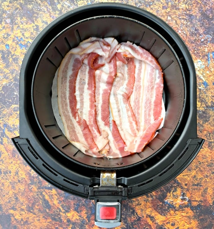 uncooked bacon in an air fryer on parchment paper