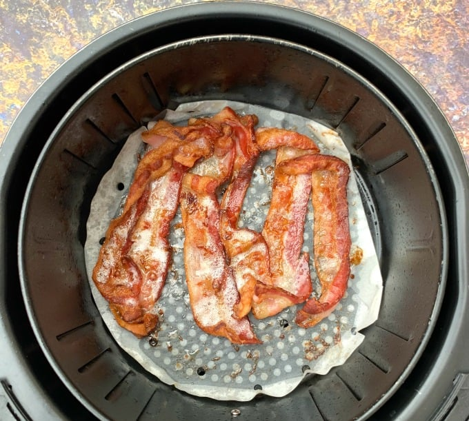 cooked bacon in an air fryer on parchment paper