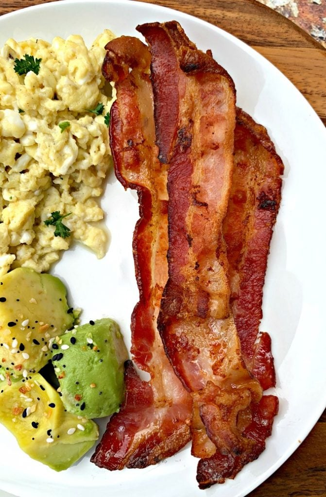 cooked air fryer bacon on a white plate with eggs and avocado