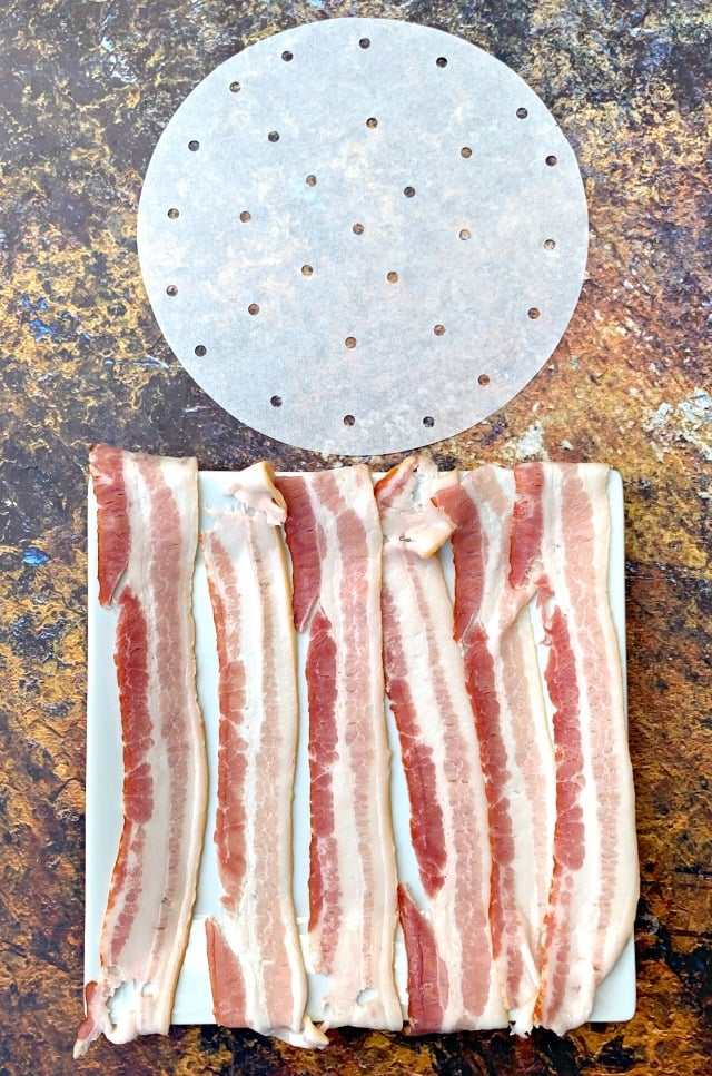 air fryer parchment paper and uncooked bacon on a white plate