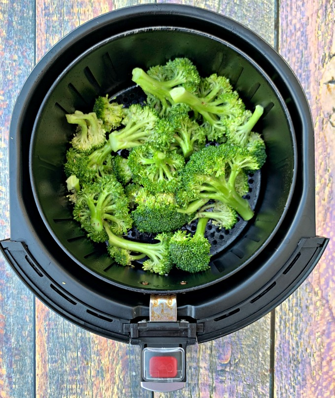 raw and cut broccoli in an air fryer