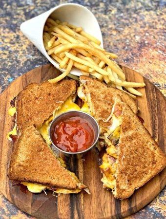 air fryer bacon grilled cheese sandwiches sliced in half with french fries