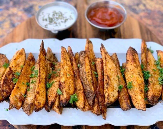 air fryer potato wedges on a white plate with ketchup and mayo