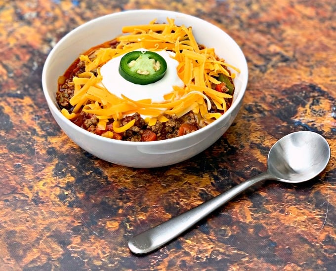 keto beef chili with shredded cheese in a white bowl with shredded cheese and sour cream