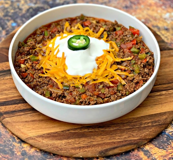 keto beef chili with shredded cheese in a white bowl with shredded cheese and sour creama