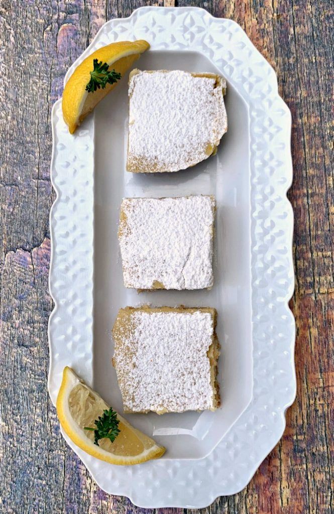 3 keto lemon bars on a white plate topped with confectioner's sugar