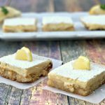 2 keto lemon bars on parchment paper with 3 lemons bars on a white plate