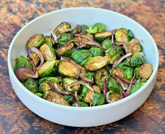 air fryer balsamic brussels sprouts with red onions in a white bowl
