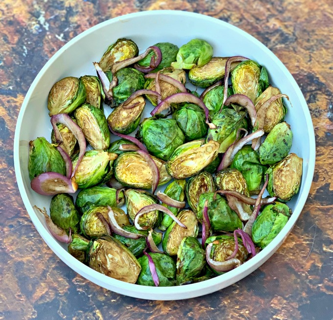 roasted air fryer balsamic brussels sprouts in an air fryer with sliced red onions