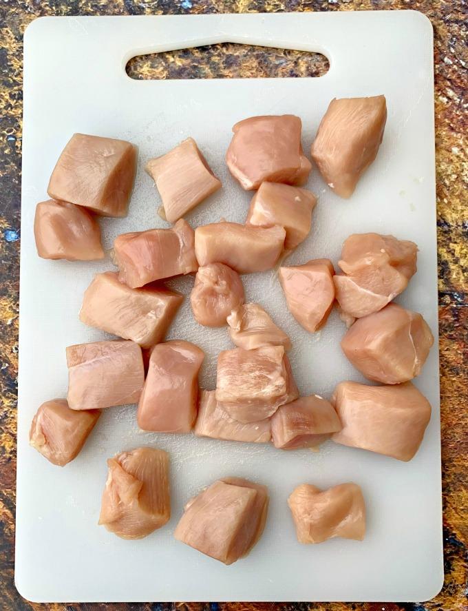 raw chicken cut into cubes on a cutting board