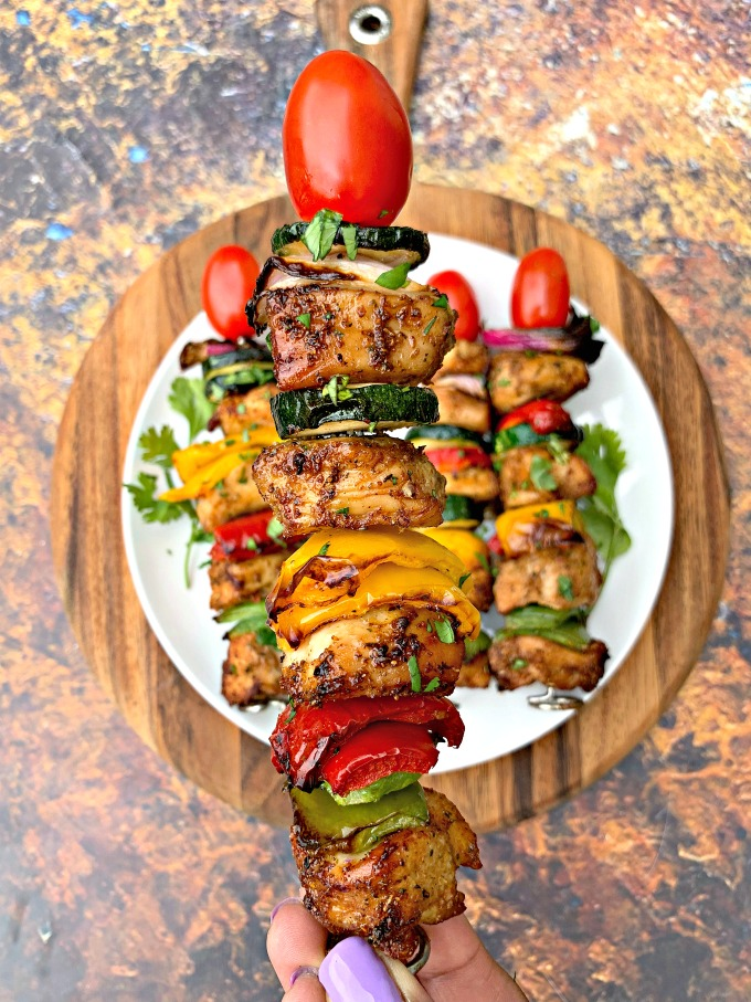 person holding air fryer grilled chicken kebobs with a skewer