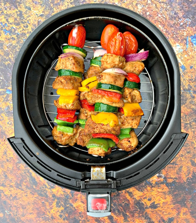 air fryer grilled chicken kebobs on a white plate in an air fryer
