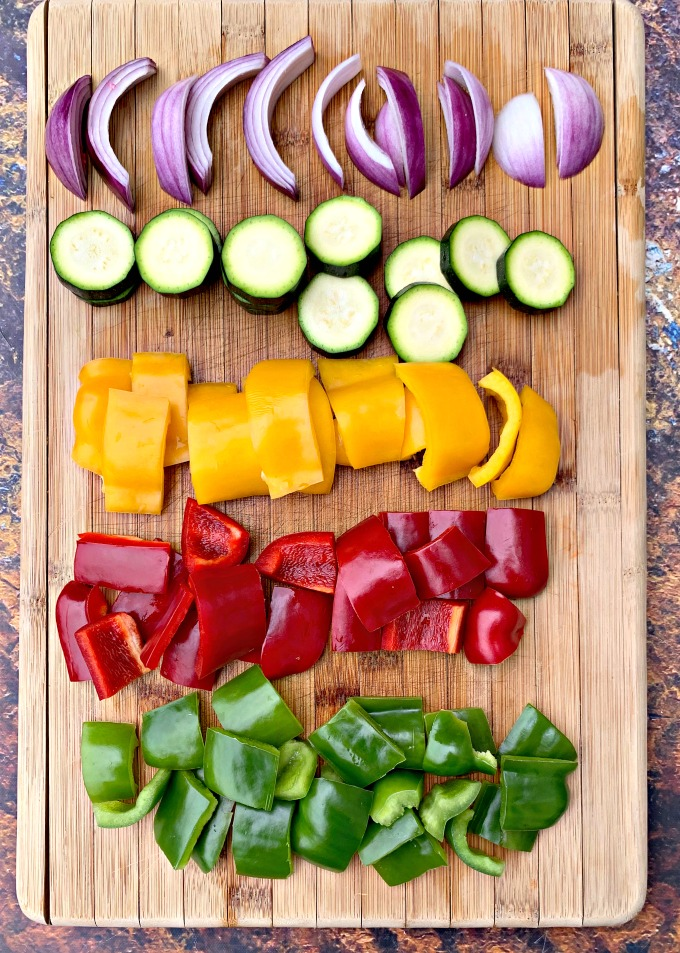 raw red peppers, green pepper, yellow peppers, zucchini, and red onions on a cutting board