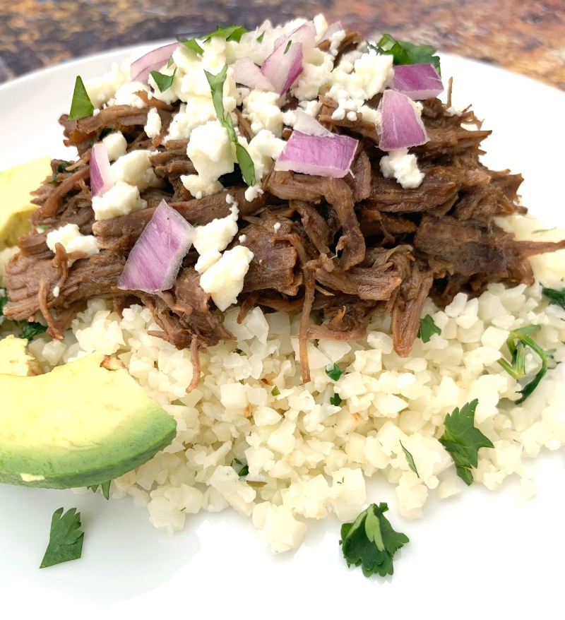 keto low carb instant pot barbacoa on top of cilantro lime cauliflower rice on a white plate