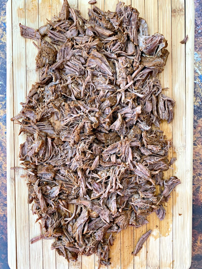 instant pot keto low carb barbacoa beef with cilantro and limes on a cutting board