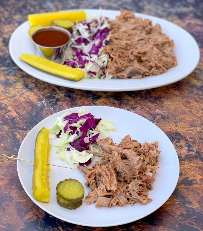 instant pot pulled pork on a plate with cabbage and pickles