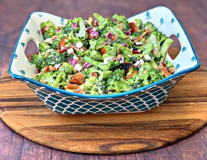 chopped broccoli with mayo, red onions, sunflower seeds, bacon, and sweetener in a blue bowl