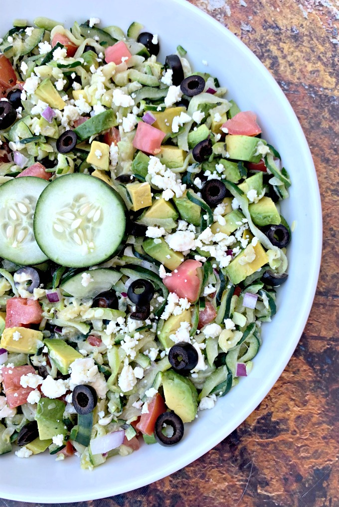 keto zucchini noodles pasta salad in a white bowl with tomatoes, olives, cucumbers, feta cheese, and red onions